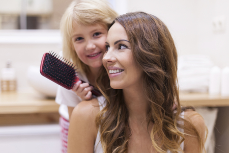 combing hair: Mother with her child in bathroom