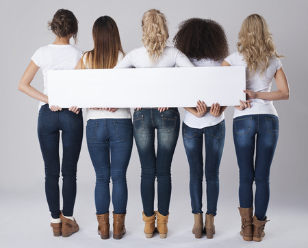 rear view girl: Girls in jeans holding empty banner