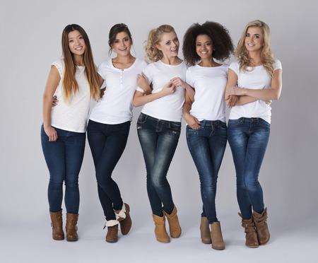 Multi-etnische vrienden dragen jeans en witte t-shirts