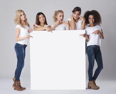 空のホワイト ボードを持つ女性の多民族グループ 写真素材