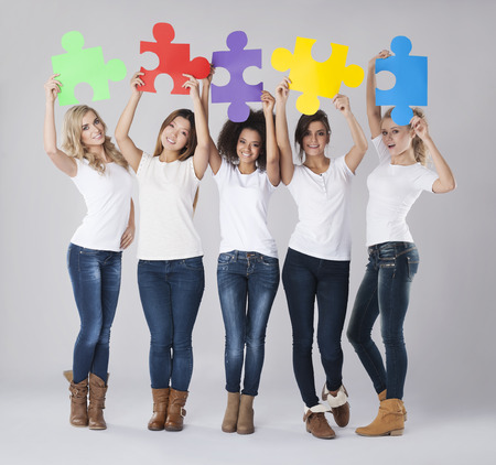 group solution: Multi ethnic girls with colored jigsaw puzzle