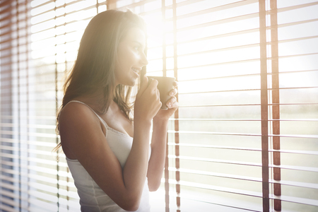 women holding cup: Morning sunshine and good coffee always makes me in a good mood