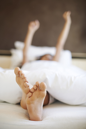 uncovering: Morning stretching in comfortable bed Stock Photo