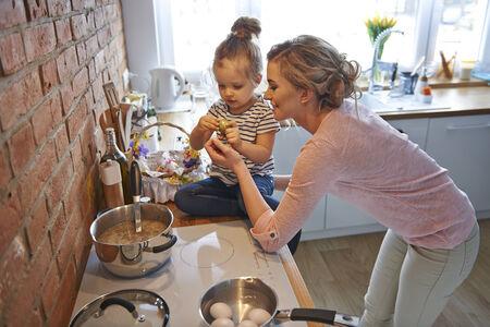 apoyo familiar: Mam� y su peque�a hija se prepara para la temporada Pascua Foto de archivo