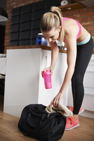 woman in towel: Packing bag for the gym
