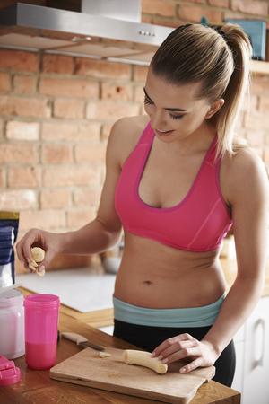 sports bra: Preparing bananas shake for active day Stock Photo