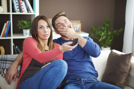 scary man: Shocked couple watching scary movie
