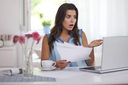 Shocked woman paying bills