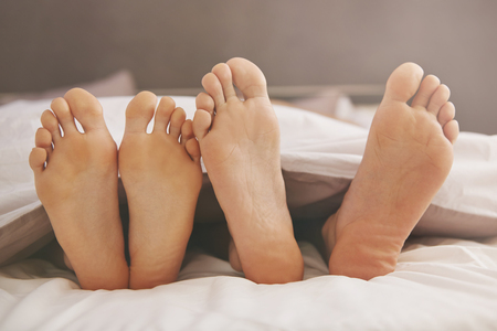 romance bed: Feet of couple in comfortable bed Stock Photo