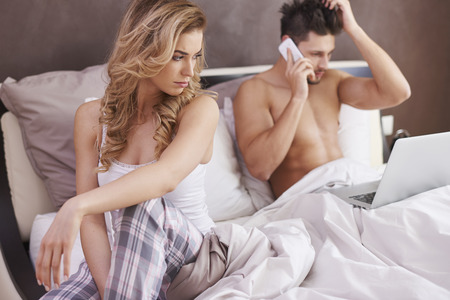 workaholic: Frustrated woman in bedroom Stock Photo