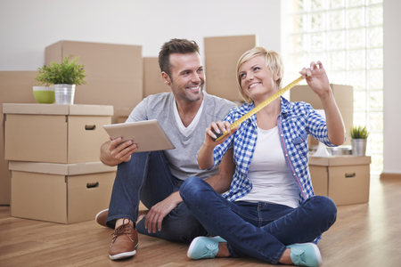 home interior: Happy couple in new house preparing room for new furniture