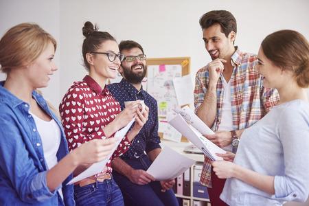 personas trabajando en oficina: El l�der del equipo feliz que tiene discusi�n con miembros de su equipo Foto de archivo