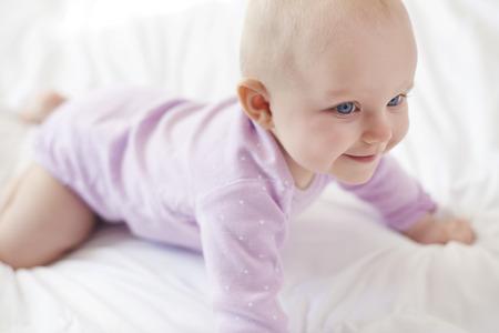 Strong cute little girl start crawling photo