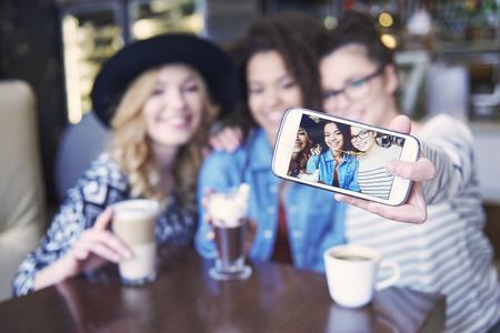 mujer tomando cafe: Echemos un selfie Foto de archivo