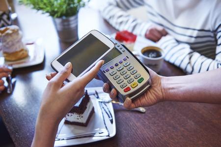 pagando: Pagar por el café por el teléfono móvil Foto de archivo