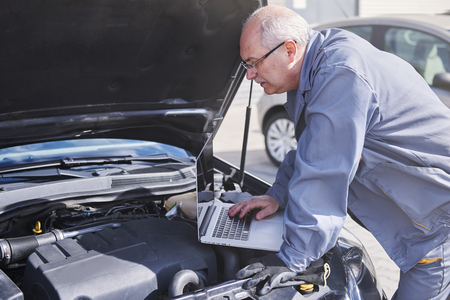 Professional mechanic using contemporary technology at work photo