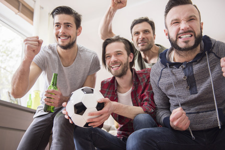 cheering people: A football brings people together Stock Photo