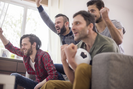 watching football: Group of friends watching football in living room