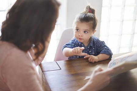 spielende kinder: Nettes Mädchen mit Mutter ein Buch zu lesen