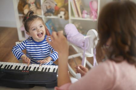 niñas jugando: Cantando y tocando instrumentos musicales con mamá