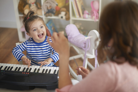 child singing: Singing and playing on musical instruments with mommy
