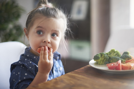 little girl child: Eating vegetables by child make them healthier