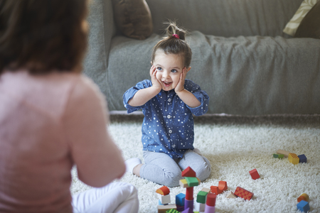 little girl sitting: Look! My tower is so high Stock Photo