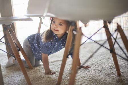 테이블 아래에 숨겨진 어린 소녀