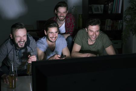 viendo television: Película divertida en la noche varonil Foto de archivo