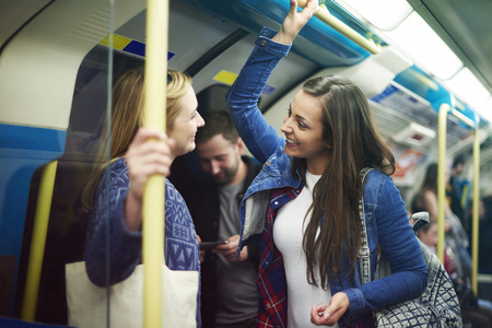 two women talking: Meeting old friends in the subway