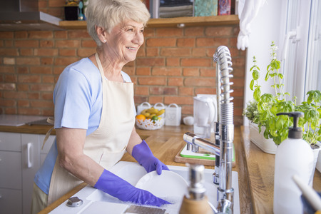 short gloves: Woman washing dishes in front of the window