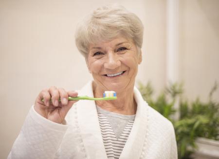 adult brushing teeth: Senior woman brushing her teeth