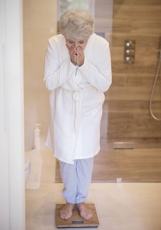 dieting: Senior woman standing on the scales Stock Photo