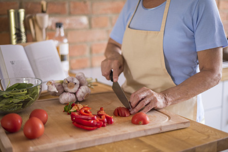obscured face: Vegetables being cutted on the cutting board
