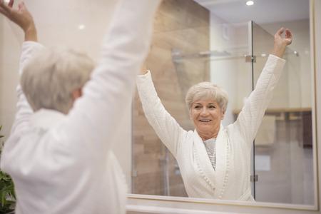 Senior vrouw met handen omhoog Stockfoto
