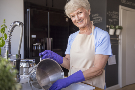 short gloves: Cheerful senior housewife in the kitchen Stock Photo