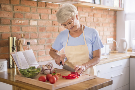 Senior woman cutting vegetables Stock Photo