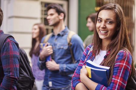 juventud: Estudiante femenino que sostiene sus libros