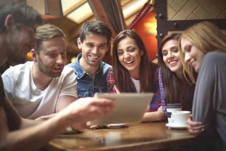 personas sentadas: Grupo de amigos en la cafeter�a