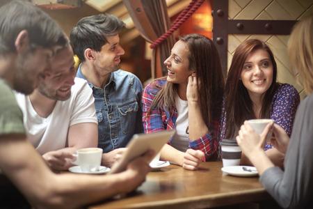 personas sentadas: Reunión en la cafetería pequeña, climático