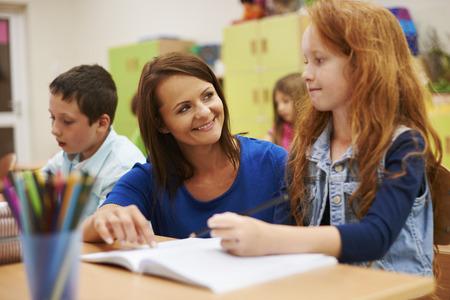 그녀의 귀여운 학생을 돕는 교사 스톡 콘텐츠