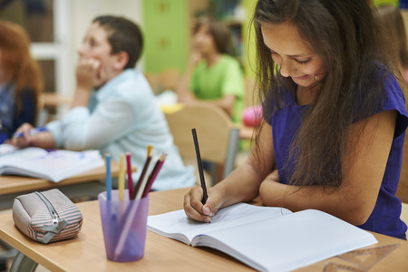 students in classroom: Girl drawing in her notebook