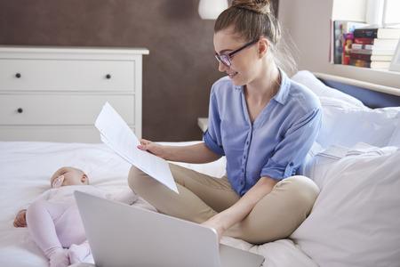 madre trabajando: Madre moderna de trabajo, mientras que su hijo est� durmiendo Foto de archivo