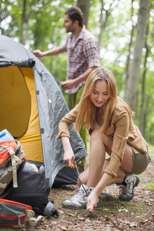 unfolding: Couple unfolding tent in the forest