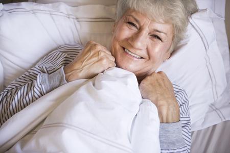 mujer descansando: Beautiful senior woman resting in the bed Foto de archivo