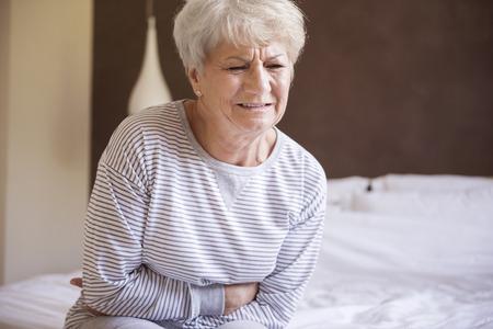 persona de la tercera edad: El dolor de la mañana de mi estómago Foto de archivo