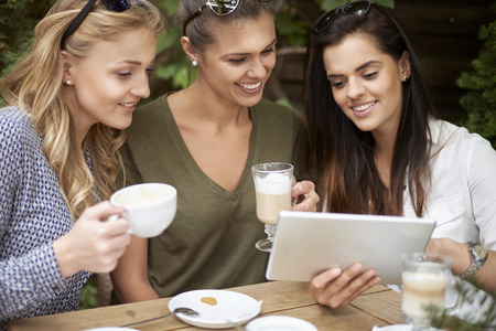 women holding cup: Enjoying the wireless internet at the cafe