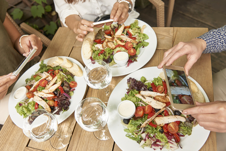 people eating restaurant: Pictures of delicious lunch in social network Stock Photo
