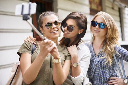 happy group: Girls posing to selfie in the city