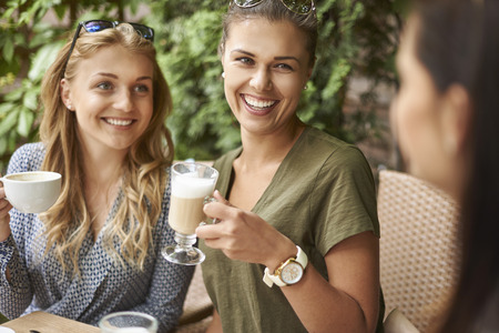 woman sitting on chair: Fresh coffee with our friends Stock Photo